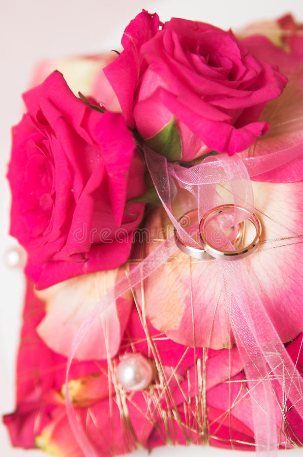 Wedding rings and flowers in soft focus royalty free stock photo