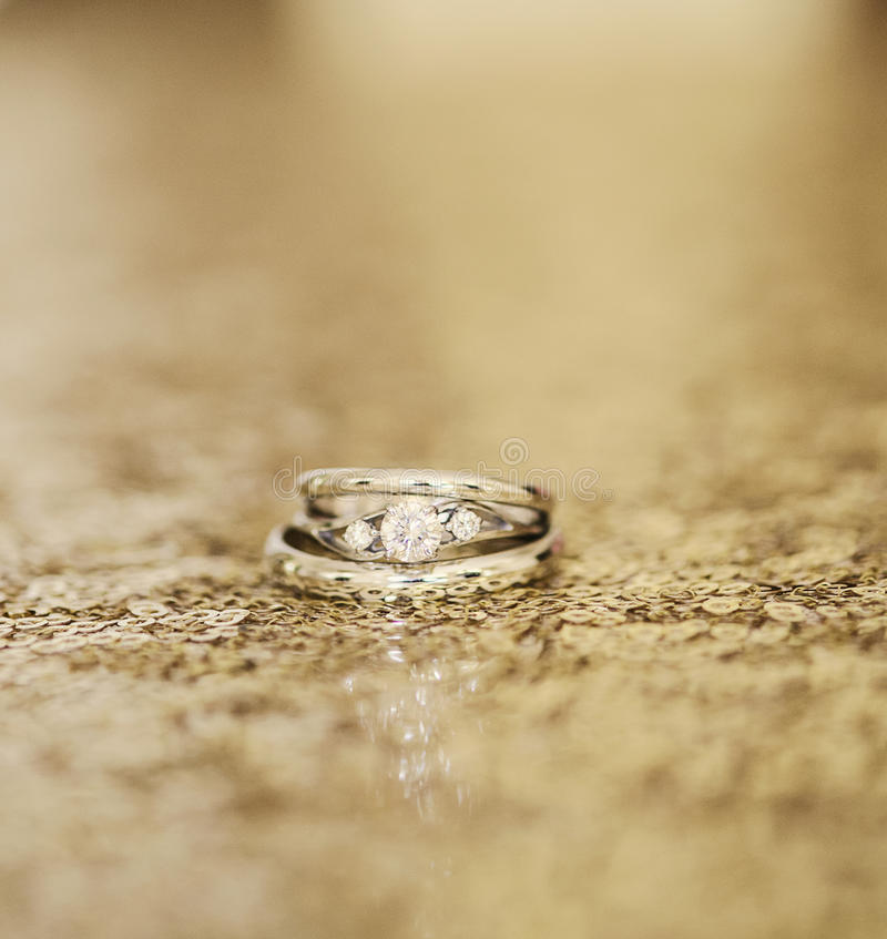 Wedding rings on gold. Sequins royalty free stock image