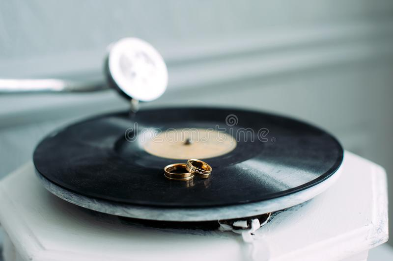 Wedding rings on the gramophone, close-up. Rings of the bride and groom on the music disc. Two gold rings on the phonograph royalty free stock images