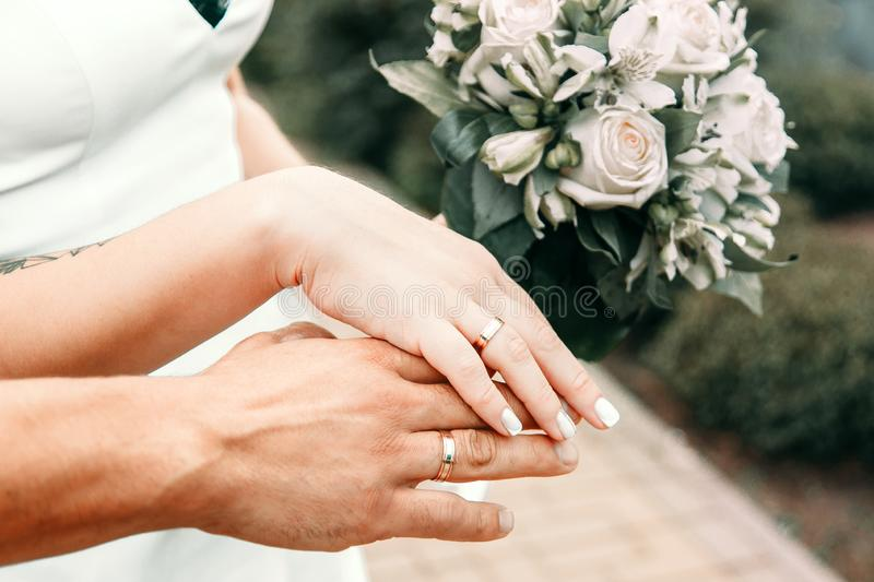Wedding rings on the hands of the bride and groom stock photos