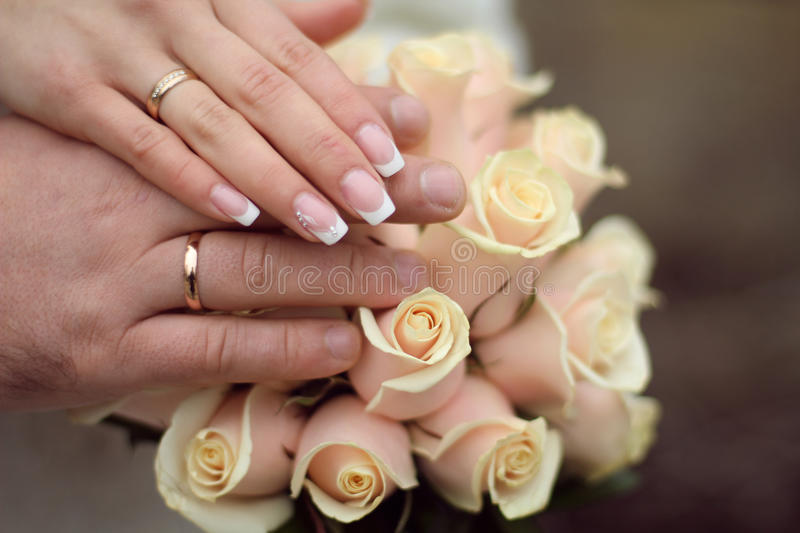 Wedding rings and Hands on roses bouquet stock images