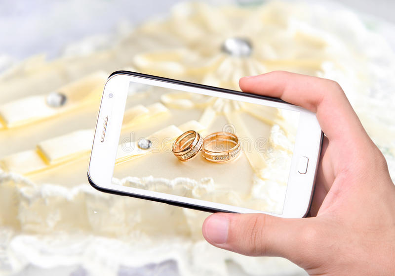 Wedding rings. Hands taking photo wedding rings with smartphone royalty free stock images