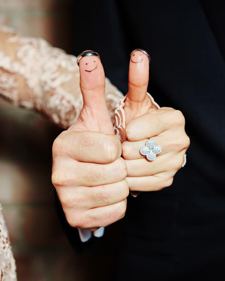 Wedding rings on her fingers painted with the bride and groom royalty free stock photos