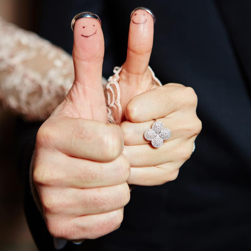 Wedding rings on her fingers painted with the bride and groom royalty free stock photo