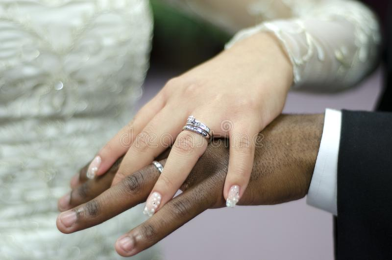 Wedding rings on interracial couple royalty free stock photos