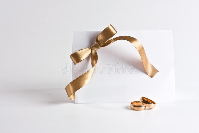 Wedding rings and invite with golden bow royalty free stock images