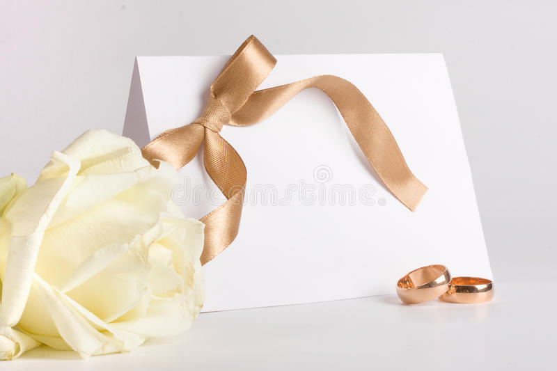 Wedding rings and invite with rose stock images