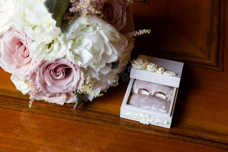 Wedding rings in a jewelry box next to a bouquet of flowers. stock photography