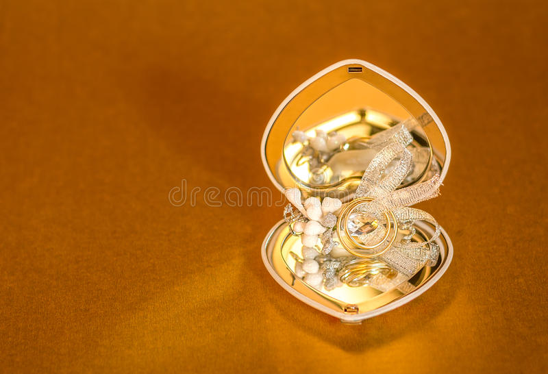 Wedding rings with jewelry decoration gold background stock photos