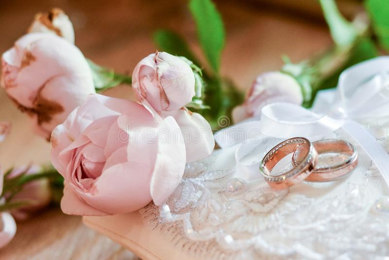 Wedding rings lie on a beautiful bouquet as bridal accessories . concept of love and marriage royalty free stock images