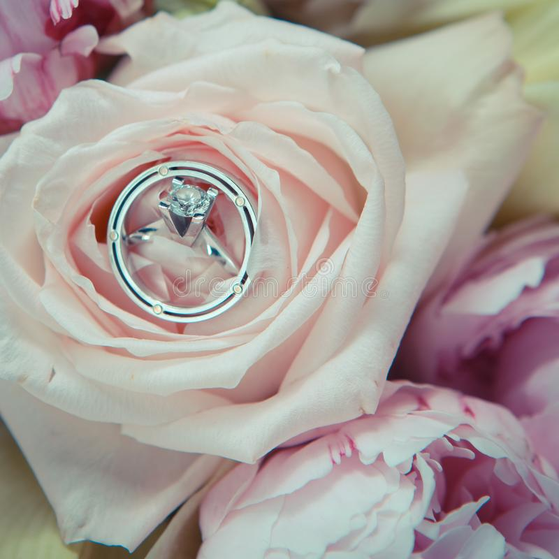 Wedding rings lie on a beautiful bouquet as bridal accessories royalty free stock photo