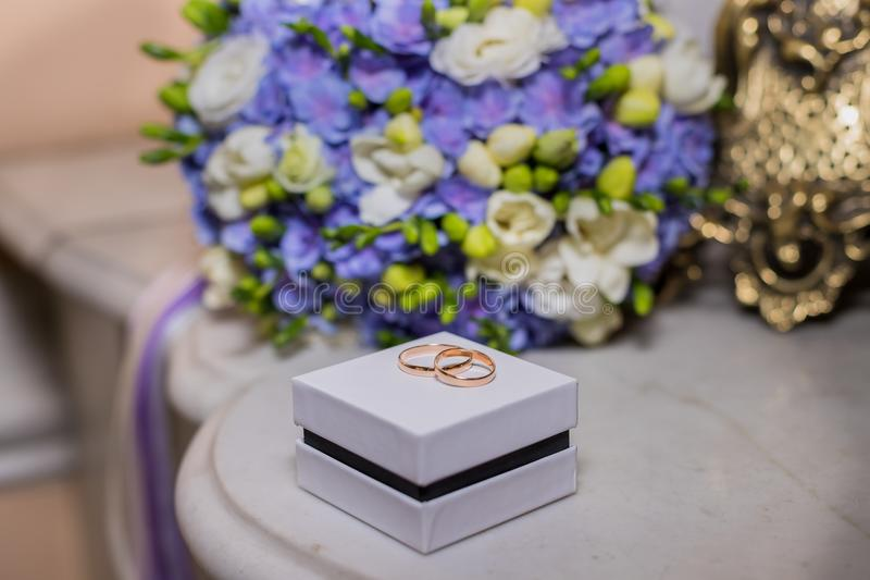 Wedding rings lie on white box on a beautiful bouquet background, as bridal accessories.solemn event, festive event royalty free stock image