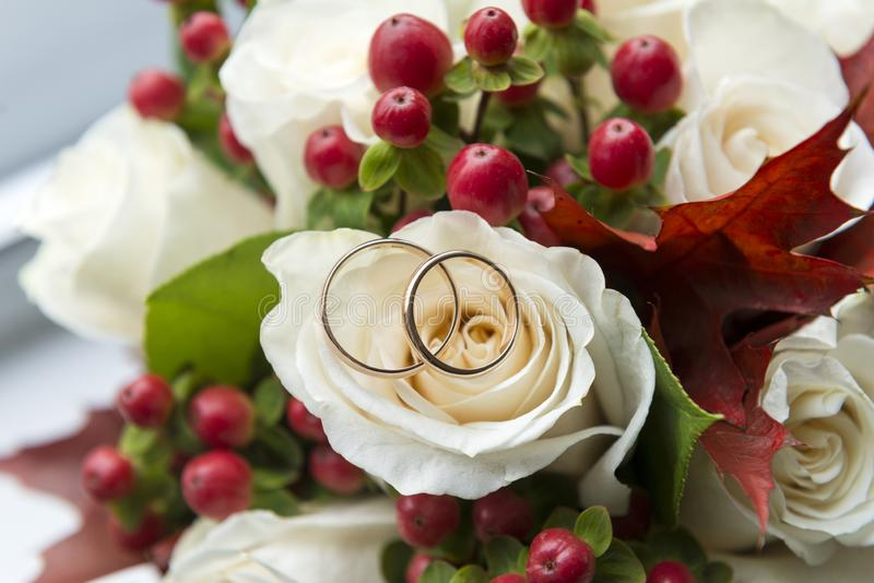 2 wedding rings lie on a bouquet of white roses, flowers royalty free stock photo