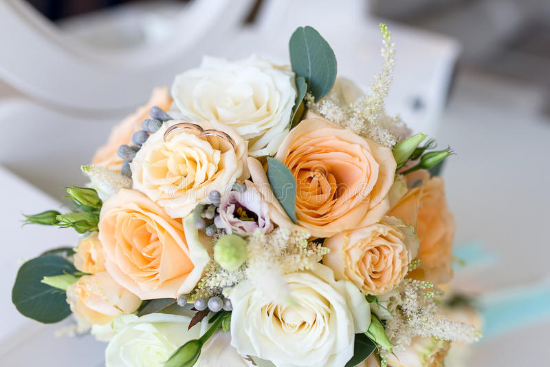 Wedding rings lie on the Bridal bouquet. Of roses. Gold wedding rings luxary royalty free stock photo