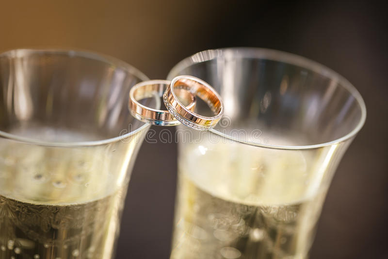 Wedding rings lie on champagne glasses. Wedding gold rings lie on champagne glasses stock photography