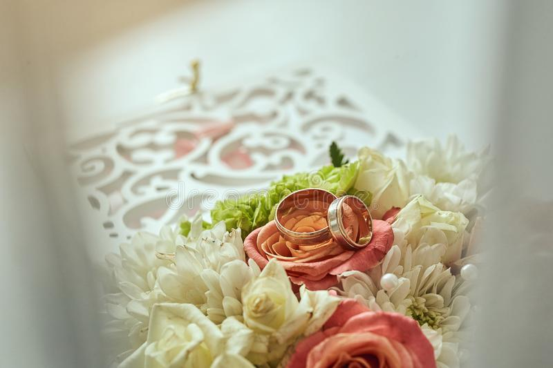 Wedding rings lie on the table near a wedding bouquet royalty free stock photo