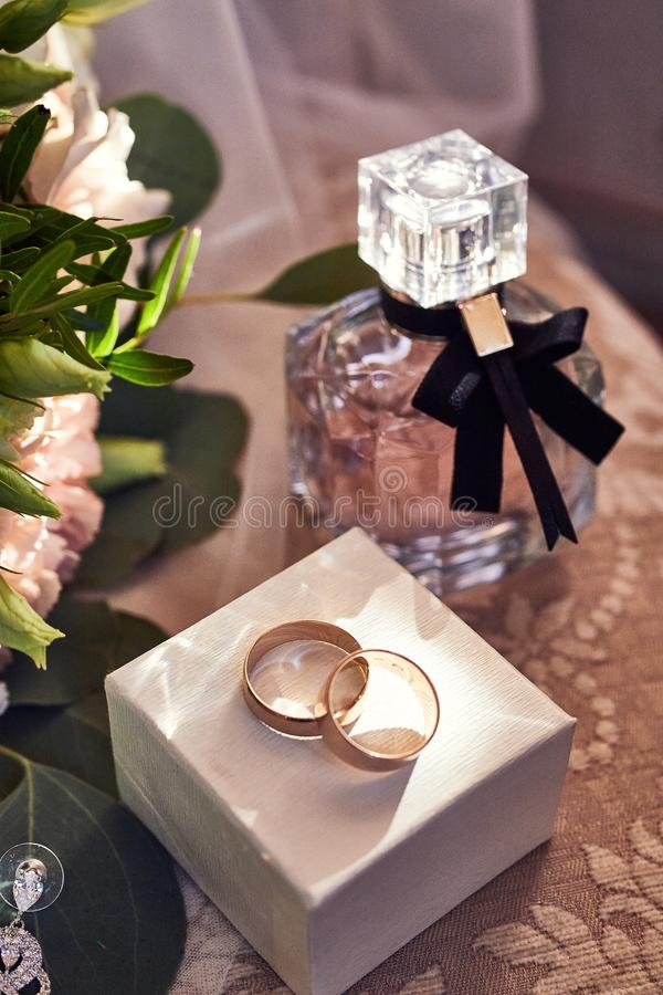 Wedding rings lie on the table near a wedding bouquet stock photo