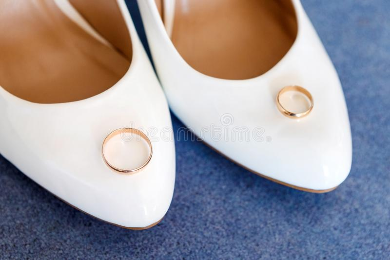 Wedding rings lie on a white bride`s shoes. Top view. Soft focus, selective focus stock photos