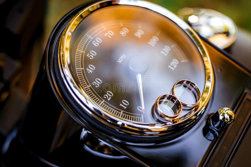 Wedding rings on a motorcycle speedometer. Wedding day royalty free stock images