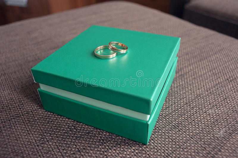 Wedding rings for the newlywed couple lie on a light green box stock photos