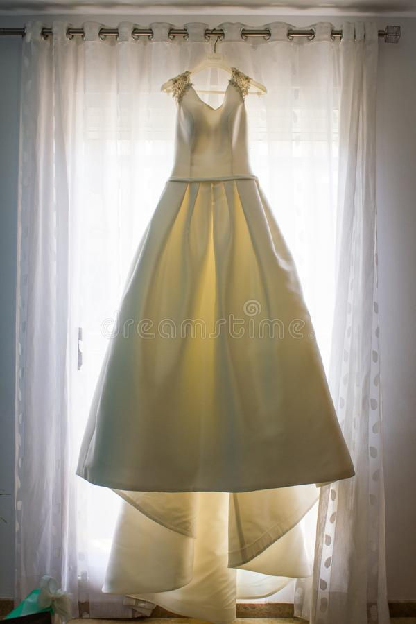Wedding dress hanging from the curtain of the bride room. On her wedding day stock photos