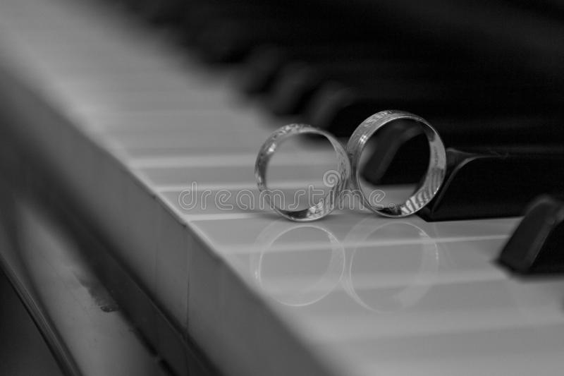 Wedding rings of piano and black and white background. stock image