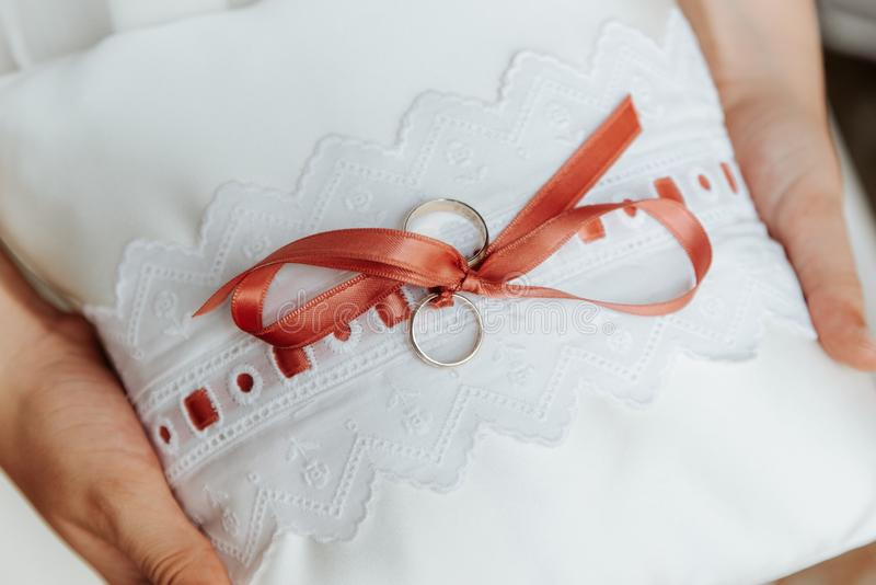 Wedding rings on a pillow with a red ribbon stock image