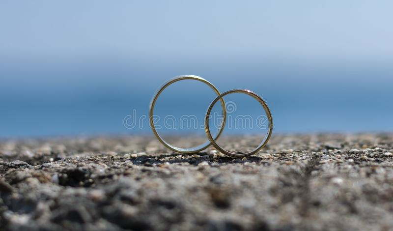 Wedding rings placed on a rock. Beautifully blue sea in the background. Shows love stock image