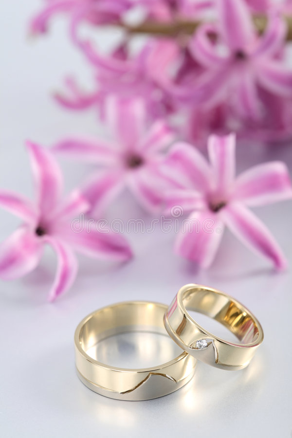 Wedding rings & purple blooms stock images
