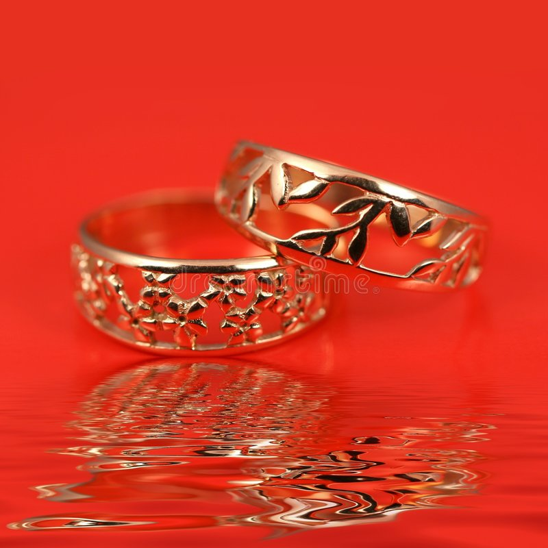 Wedding rings on red background. A pair of gold wedding rings on red background and water ripples stock photography