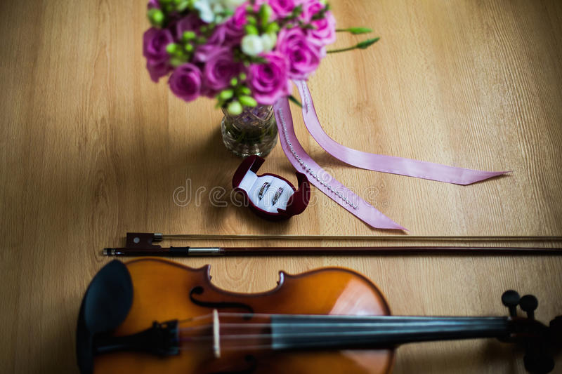 Wedding rings in the red box, a violin and bow, wedding flowers, wedding bouquet of beautiful pink roses and white flowers royalty free stock image