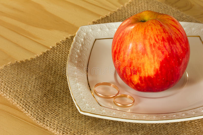 Wedding rings and red ripe Apple royalty free stock photos
