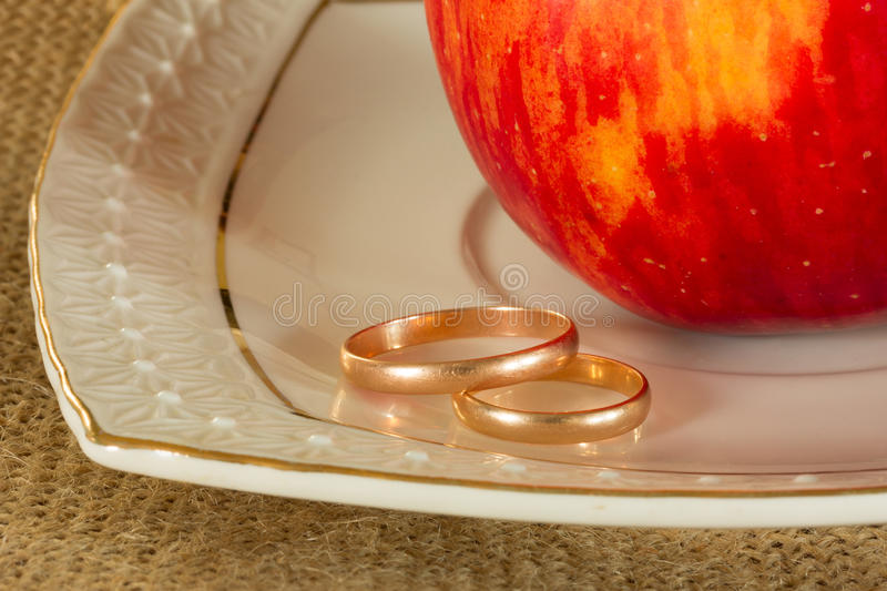 Wedding rings and red ripe Apple stock images