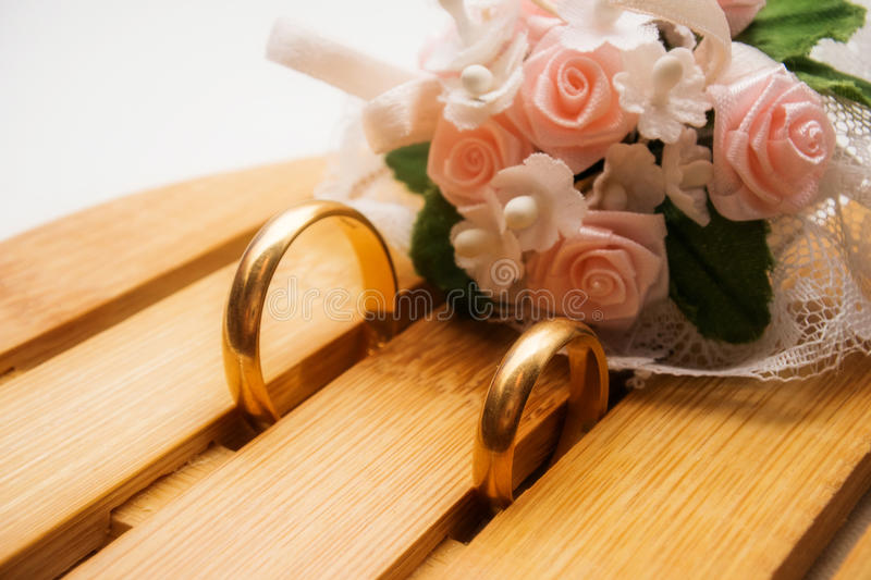 Wedding rings and roses bouquet stock photos