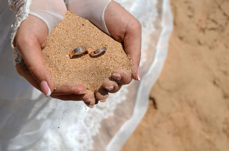 Wedding rings on the sand in the hands of the bride on the beach royalty free stock photo