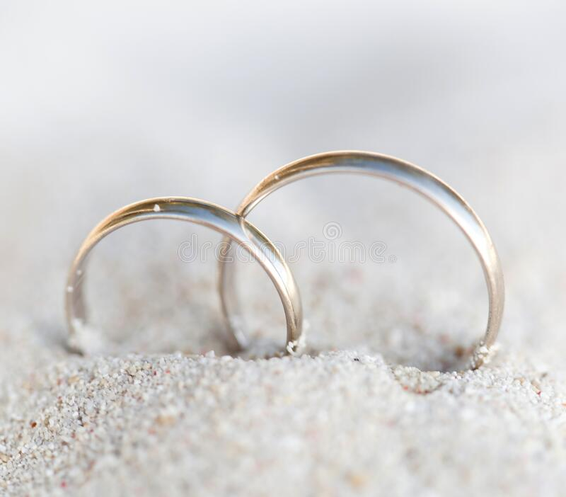 Wedding rings in sand on beach stock photography