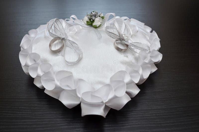 Wedding rings on satin pillow stock photos