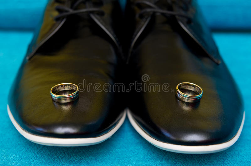 Wedding rings on shoes. Wedding rings with names engraved lying on black groom shoes stock photo