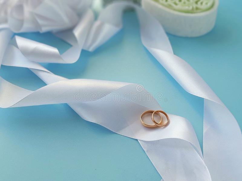 Wedding rings on silk ribbons on blue background. Selective focus. Place for text royalty free stock photo