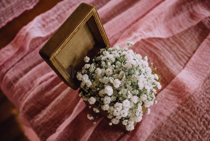 Wedding rings small white flowers wooden box stock photo