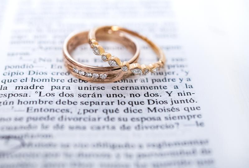 Wedding rings and Spanish Bible scripture. Husband and wife marriage wedding band. Gold with diamonds. Resting on top of Spanish translation Holy Bible, Santa stock image