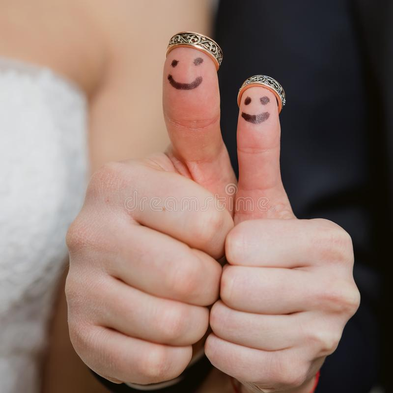 Wedding rings on their fingers painted with the bride and groom, funny little people stock photos