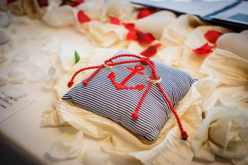 Wedding rings together with red rope on striped pillow with anchor on it. Marriage ceremony stock photo