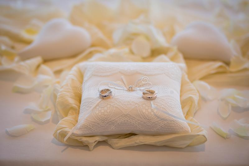 Wedding rings together with white rope on white pillow surrounded white hearts. Marriage ceremony royalty free stock photography