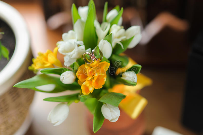 Wedding rings on a tulips bouquet stock photography