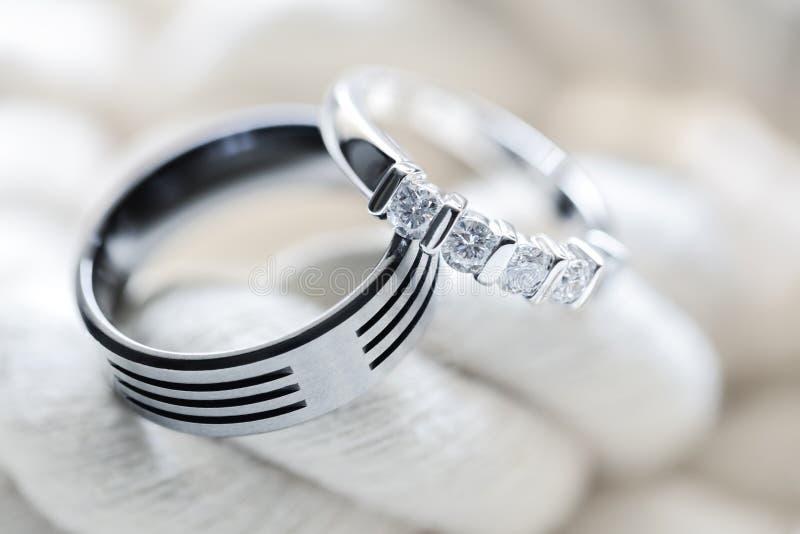 Wedding rings. Two silver platinum and titanium diamond wedding rings on white rope background stock photos