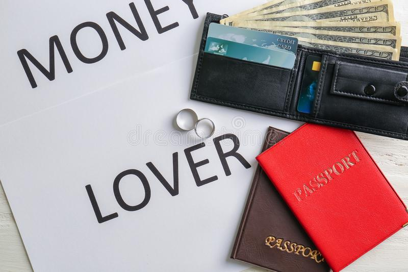Wedding rings, wallet with dollars, passports and card with text MONEY LOVER on table. Marriage of convenience royalty free stock photo