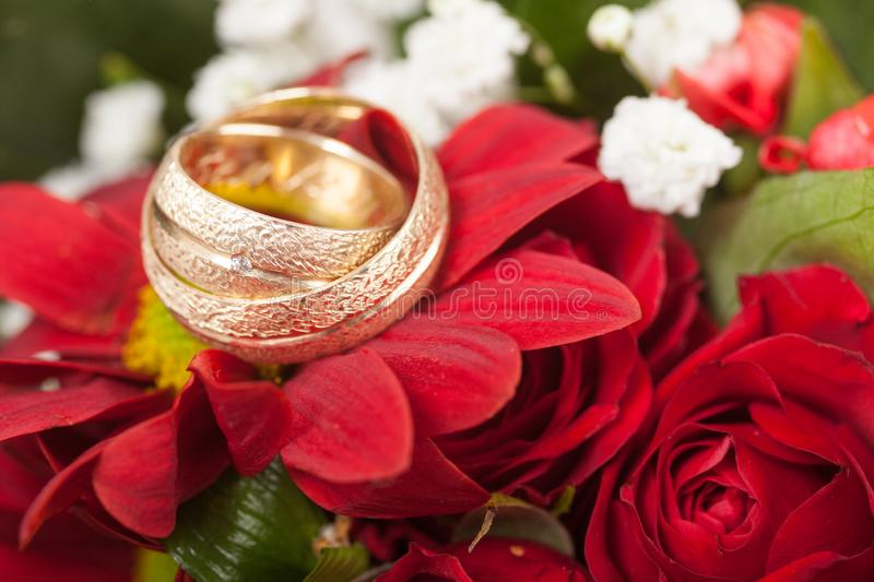 Wedding rings on a wedding bouquet of rouses. Wedding background stock photography