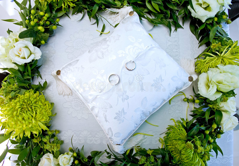 Wedding rings on a white cushion in a wreath of flowers royalty free stock photo