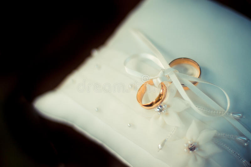 Wedding rings on a white pillow. Gold rings, symbol of love. Wedding concept on a dreamy background stock photos